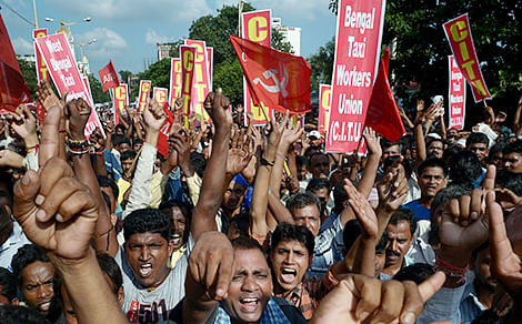 Taxi drivers shout slogans against the state government during a rally in Kolkata on Monday.  	-AFP