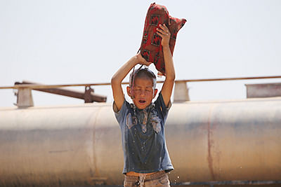 An Iraqi Yazidi refugee pours water on himself as he took refuge in Syria.