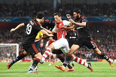 Ten-man Arsenal edge through