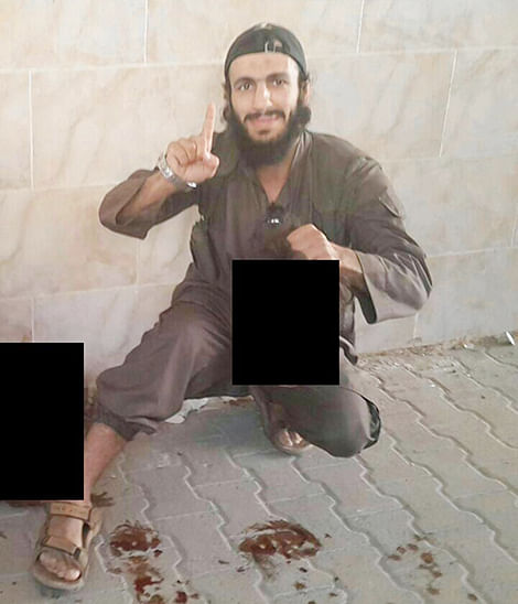 Mohamed Elomar is seen holding up the decapitated head a man. Another head is lying next to him.
