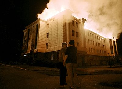 Bystanders watch fire consuming a school in downtown Donetsk on Thursday after being hit by a shelling.