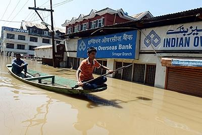 Kashmiri youth rowing a shikara boat past a flood-inundated bank near Dal Lake in Srinagar.  A small army of fellow shikara owners, who normally ferry holidaymakers, have spent the last five days rescuing those stranded on sinking houseboats and bringing them to safety.