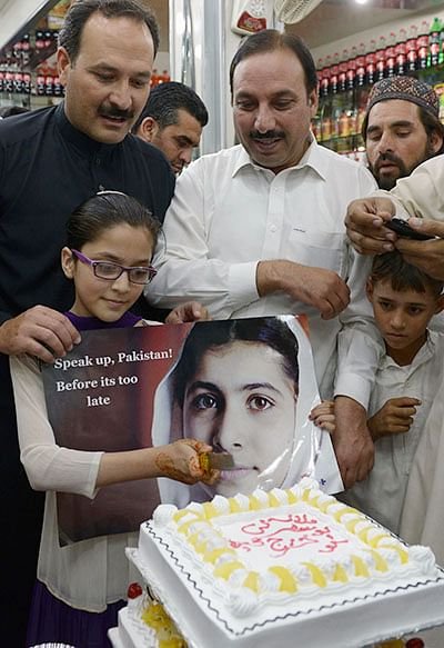 A Pakistani girl holds a photograph of child  education activist Malala Yousafzai as she cuts a cake in celebration of Malala winning the Nobel Peace Prize, in Malala's hometown Mingora in Swat valley.