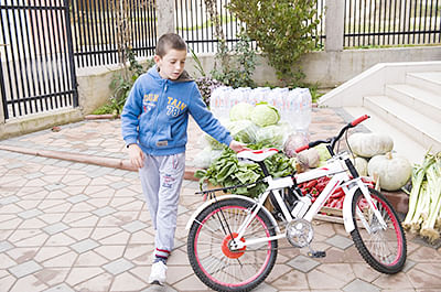 Kosovar Erion Zena, 8, who was taken to Syria by his  father who joined jihadist, parks his bike outside a store in Pristina. Zena had been brought home on October 15  after an operation by Kosovo Intelligence Agency.