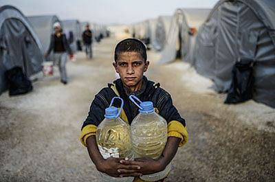 A Syrian Kurdish boy carries  water to his  family's tent in  a refugee camp in Sanliurfa province.