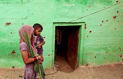 A villager carries her child past a house riddled with bullets in Jammu on Tuesday.