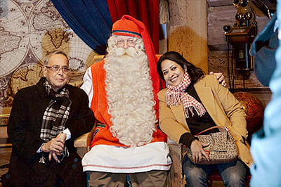President Pranab Mukherjee and his daughter Sharmistha Mukherjee with a Santa Claus during a visit to Rovaniemi, official Santa Claus Village in Arctic Circle on Thursday.