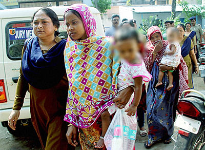 A police woman escorts two women with their children, accused in Burdwan blast, on the way to CID headquarters in Kolkata in Burdwan on Wednesday.