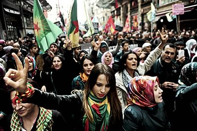 Turkish Kurds shout slogans and flash the victory signs during a demostration in Istanbul, as part of an international day organised in support of Kurdish fighters trying to repel the Islamic State (IS) group in the Syrian border town of Kobane.