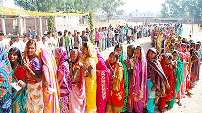 Voters wait to cast their votes at a polling station during the first phase of Jharkhand assembly polls, in Latehar.
