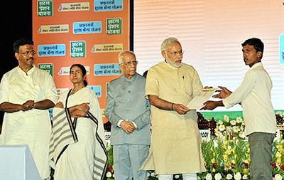 Prime Minister Narendra Modi presenting the Insurance policies to the beneficiaries of the Social Security Schemes, at Nazrul Manch, in Kolkata on Saturday. Governor of West Bengal,  Keshari Nath Tripathi and Chief Minister  Mamata Banerjee is also seen.PTI