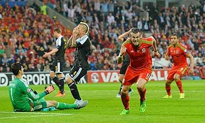 Wales's midfielder Gareth Bale (2R) celebrates scoring the opening goal as Belgium's goalkeeper Thibaut Courtois (L) and Belgium's midfielder Radja Nainggolan (2L) react during the Euro 2016 qualifying group B football match between Wales and Belgium at Cardiff City Stadium in Cardiff, south Wales, on June 12, 2015.  AFP PHOTO / GLYN KIRK
