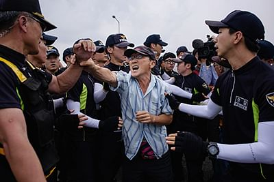 Anti-North Korean activists (C) struggle with police as they protest on the Unification Bridge that leads to the Demilitarized Zone (DMZ) between North and South Korea in Paju on August 24, 2015. South Korea's president hardened her line with North Korea on August 24, demanding an unequivocal apology for recent provocations as the two rivals struggled to negotiate their way out of a dangerous military standoff.      AFP PHOTO / Ed Jones