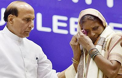 New Delhi: Home Minister Rajnath Singh honours a brave mother of BSF martyr to paying tribute during the BSF Golden Jubilee Year celebrations in New Delhi on Wednesday. PTI Photo by Vijay Verma (PTI10_21_2015_000246B)
