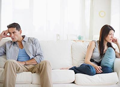 Angry mixed race couple having argument on sofa