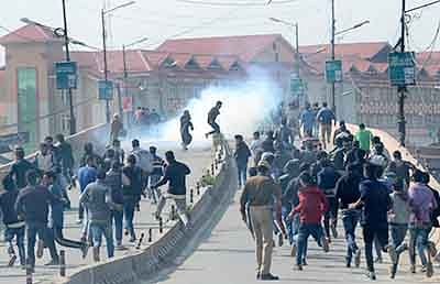 Kashmiri Shiite Muslimis run after Indian police fire tear-smoke shells as devotees defy restrictions for a Muharram procession in Srinagar on October 22, 2015.  Authorities imposed restrictions in parts of Srinagar, the summer capital of Kashmir, to thwart planned Muharram processions as police detained more than a dozen protesters and fired teargas to disperse participants.  AFP PHOTO/ Tauseef MUSTAFA