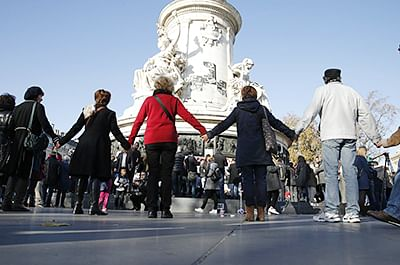 People join hands as they stand around the Monument a la Republique in Paris, on November 15, 2015, two days after the deadly attacks in which at least 128 people were killed. Islamic State jihadists claimed a series of coordinated attacks by gunmen and suicide bombers in Paris that killed at least 128 people in scenes of carnage at a concert hall, restaurants and the national stadium.  AFP PHOTO / PATRIK KOVARIK