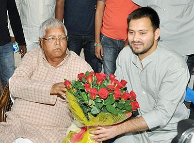 Patna: RJD chief Lalu Prasad greeting his son and RJD leader Tejaswi Yadav on his birthday in Patna, Bihar, on Monday.  PTI Photo(PTI11_9_2015_000159B)