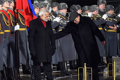 RPT--Moscow : A Russian official nudging Prime Minister Narendra Modi as he walks past a guard of honour even as the Indian national anthem was being played during his arrival at Vnukovo-2 Airport in Moscow on Wednesday. PTI Photo by Shahbaz Khan (PTI12_23_2015_000324B)