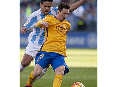 Malaga's midfielder Jose Luis Garcia Recio (L) vies with Barcelona's Argentinian forward Lionel Messi during the Spanish league football match Malaga CF vs FC Barcelona at La Rosaleda stadium in Malaga on January 23, 2016.  AFP PHOTO / JORGE GUERRERO