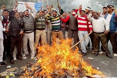 New Delhi: MCD workers burning effigies during a protest over their demands  at Civil Lines in New Delhi on Friday. PTI Photo (PTI1_29_2016_000147B)