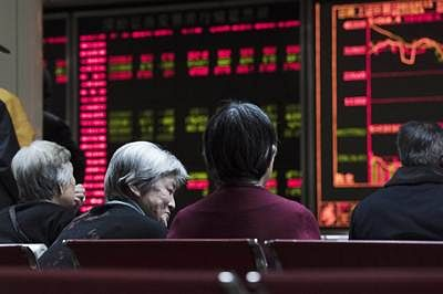 Investors look at screens showing stock market movements at a securities company in Beijing on January 13, 2016. Shanghai stocks gave up early gains on January 13 to end the morning flat despite a better-than-expected trade report out of China, but Hong Kong rallied.       AFP PHOTO / FRED DUFOUR