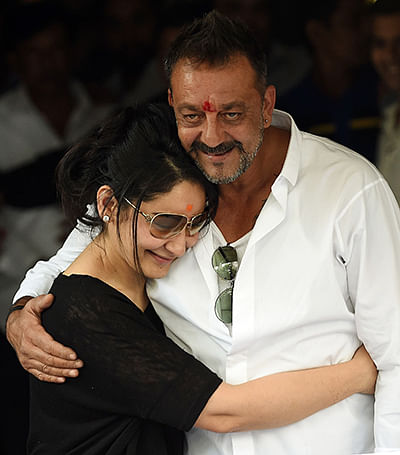 Indian Bollywood actor Sanjay Dutt (R) hugs his wife Manyata Dutt outside their home in Mumbai on February 25, 2016, after his release from Pune's Yerwada Jail. Bollywood actor Sanjay Dutt was released from prison after serving about four years for possessing weapons supplied by gangsters behind a series of bomb blasts in Mumbai in 1993. The disgraced star kissed the ground as he walked free from the jail in the western city of Pune, after authorities decided to release him ahead of schedule for good behaviour.  AFP PHOTO / PUNIT PARANJPE