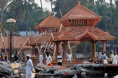 Kollam: People check out the damaged structures after a massive fire broke out Sunday during a fireworks display at the Puttingal temple complex in Paravoor village, Kollam district on Monday. PTI Photo (PTI4_11_2016_000434B)