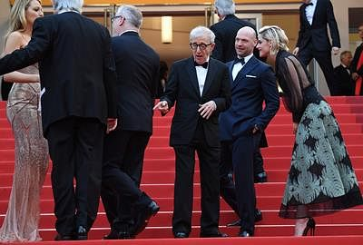 "US director Woody Allen (C) gestures as he arrives on May 11, 2016 with US actor Corey Stoll (2ndR) and US actress Kristen Stewart (R) for the screening of the film ""Cafe Society"" during the opening ceremony of the 69th Cannes Film Festival in Cannes, southern France.  / AFP PHOTO / ANNE-CHRISTINE POUJOULAT"