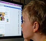 E7ANG3 Child children boy looking at Facebook on home computer social media Uk