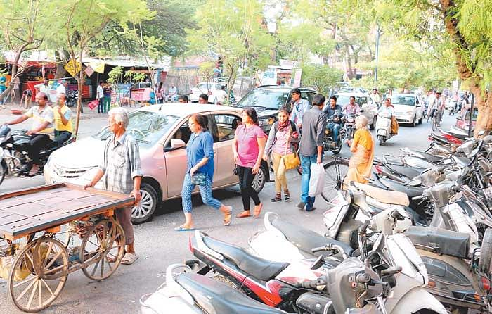 Two-wheelers parked on footpath and road forcing pedestrians to walk on the road.