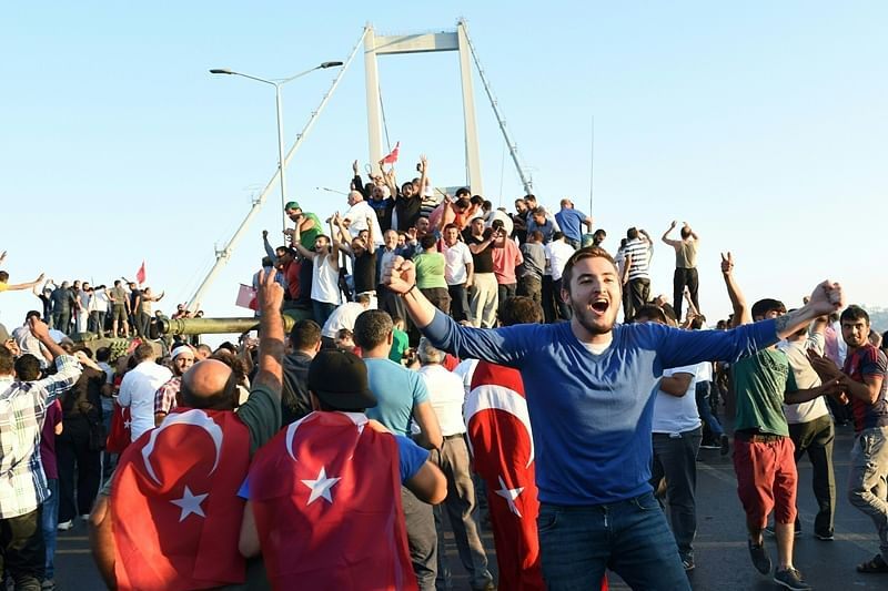EDITORS NOTE: Graphic content / People react after they take over military position on the Bosphorus bridge in Istanbul on July 16, 2016.  At least 60 people have been killed and 336 detained in a night of violence across Turkey sparked when elements in the military staged an attempted coup, a senior Turkish official said. The majority of those killed were civilians and most of those detained are soldiers, said the official, without giving further details.   / AFP PHOTO / Bulent KILIC