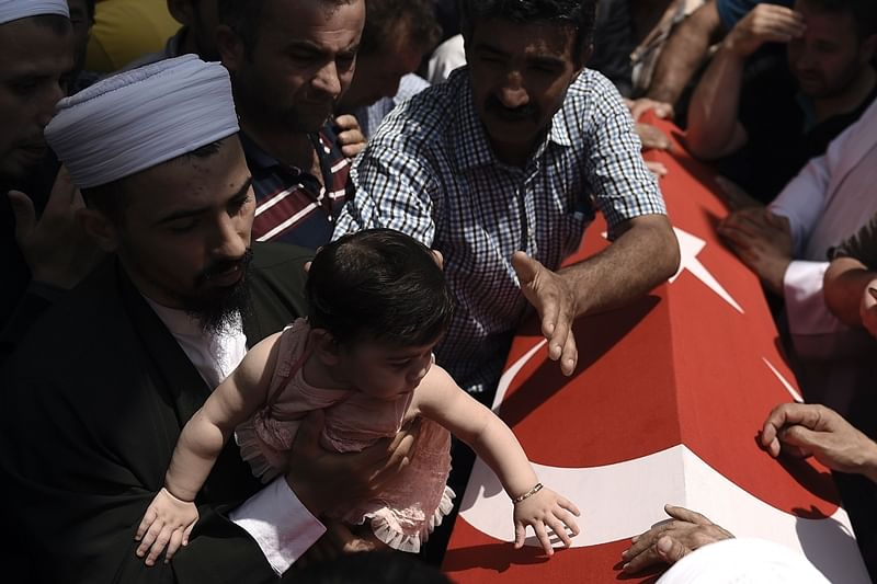 "A man holds a baby girl near the flag-draped coffin of a relative as he mourns in Istanbul on July 17, 2016, during the funeral of seven victims of the July 15 coup attempt.  Turkish President Recep Tayyip Erdogan vowed on July 17 to purge the ""virus"" within state bodies, during a speech at the funeral of victims killed during the coup bid he blames on his enemy Fethullah Gulen. / AFP PHOTO / ARIS MESSINIS"