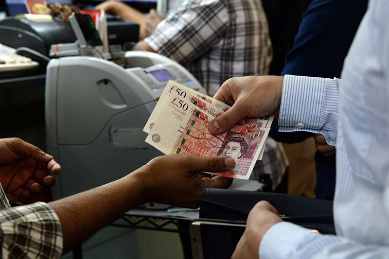 A man buys British pound from a money changer at in Singapore on June 24, 2016.  The pound nosedived to the 1.33 USD level on June 24 as the unit took a beating on fears that Britain will vote to leave the European Union, in what critics warned would be a hammer blow to financial markets. / AFP PHOTO / ROSLAN RAHMAN