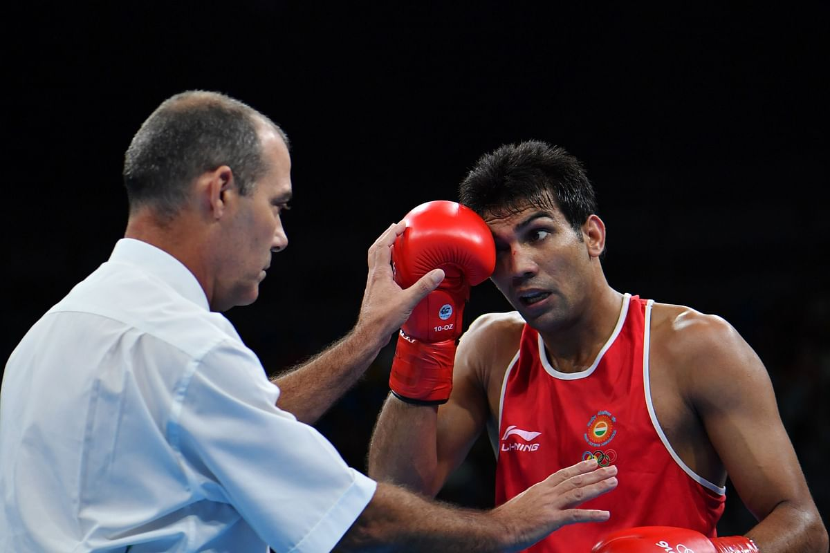 A referee attends to India's Manoj Kumar (R) as he fights Lithuania's Evaldas Petrauskas during the Men's Light Welter (64kg) match at the Rio 2016 Olympic Games at the Riocentro - Pavilion 6 in Rio de Janeiro on August 10, 2016.   / AFP PHOTO / Yuri CORTEZ