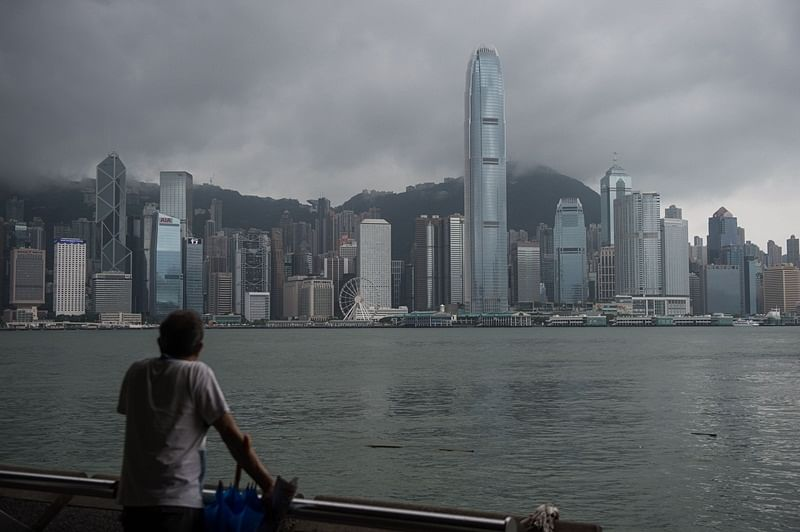 "A man looks out towards the skyline from a promenade overlooking Victoria Harbour in Hong Kong on August 2, 2016, as storm clouds pass during a ""T8"" storm signal raised for Typhoon Nida.  Hong Kong shut down on August 2 as Typhoon Nida brought violent winds and torrential rain, with hundreds of flights cancelled and the stock market, schools and businesses closed, as the storm headed across southern China."