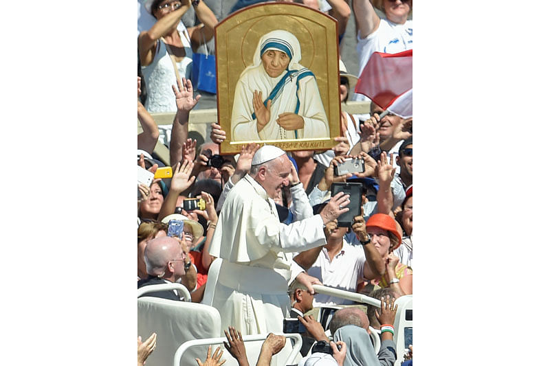 Pope Francis (C) waves to faithful as he leaves after a Holy Mass and canonisation of Mother Teresa of Kolkata, on Saint Peter's Square in the Vatican, on September 4, 2016. Mother Teresa, the nun whose work with the dying and destitute of Kolkata made her a global icon of Christian charity, was made a saint on September 4, 2016. Her elevation to Roman Catholicism's celestial pantheon came in a canonisation mass in St Peter's square in the Vatican that was presided over by Pope Francis in the presence of 100,000 pilgrims.  / AFP PHOTO / ANDREAS SOLARO