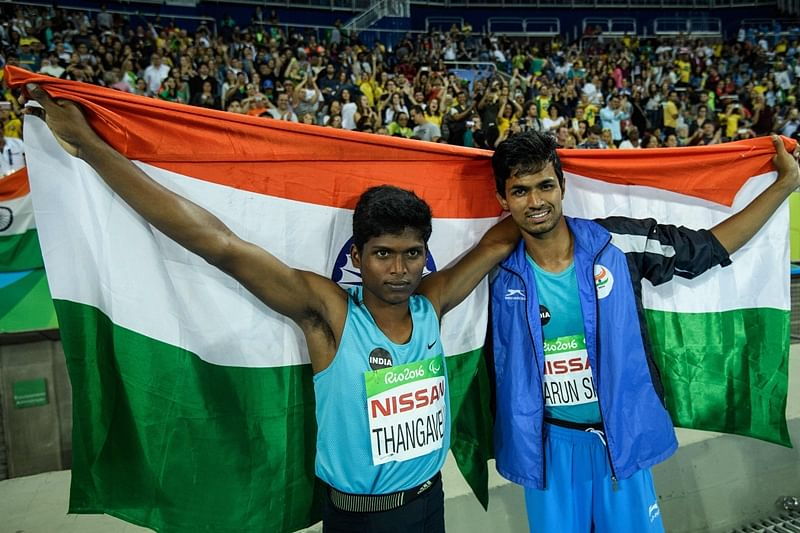 India's Mariyappan Thangavelu (L) and Bhati Varun Singh celebrate their gold and bronze medals, respectively, after the men's final high jump - T42 during the Paralympic Games at the Olympic Stadium in Rio de Janeiro on September 9, 2016. / AFP PHOTO / YASUYOSHI CHIBA