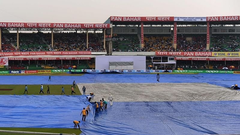 Ground staff cover the pitch as rain halts play on the second day of the first cricket test match between India and New Zealand at Green Park Stadium in Kanpur on  September 23, 2016.  / AFP PHOTO / PRAKASH SINGH / ----IMAGE RESTRICTED TO EDITORIAL USE - STRICTLY NO COMMERCIAL USE----- / GETTYOUT