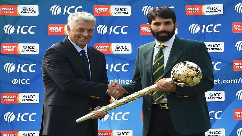 Pakistan cricket captain Misbah-ul-Haq (R) receives a ICC Test Championship mace from ICC Chief Executive David Richardson in Lahore on September 21, 2016. Pakistan achieved the number one ranking in the Test Championship table after the Test match series drawn 2-2, between England and Pakistan at the Oval in London on August 14, 2016. / AFP PHOTO / ARIF ALI