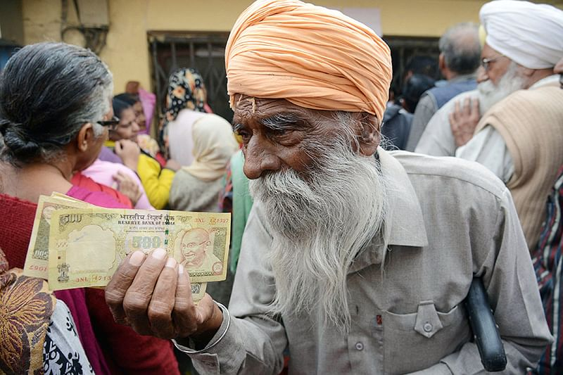 Senior citizens gather outside a bank as they wait to deposit and exchange 500 and 1000 rupee notes in Amritsar on November 19, 2016.