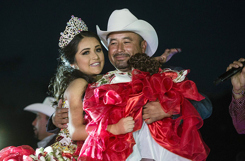 Rubi Ibarra (L) dances with her father Cresencio Ibarra during her 15th birthday celebrations in Villa de Guadalupe, San Luis Potosi State, Mexico on December 26, 2016.  Rubi, a small-town Mexican teen, welcomed thousands of guests for her 15th birthday party after her parents' video invitation to the milestone event went viral online.   / AFP PHOTO / Mauricio PALOS