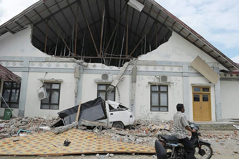 TOPSHOT - a man rides past a district hospital which was damaged after an earthquake in Pidie Jaya, Aceh province on December 7, 2016.  At least 52 people were killed and hundreds injured on December 7 after a strong earthquake struck Indonesia's Aceh province, with officials warning the death toll would likely rise. / AFP PHOTO / CHAIDEER MAHYUDDIN