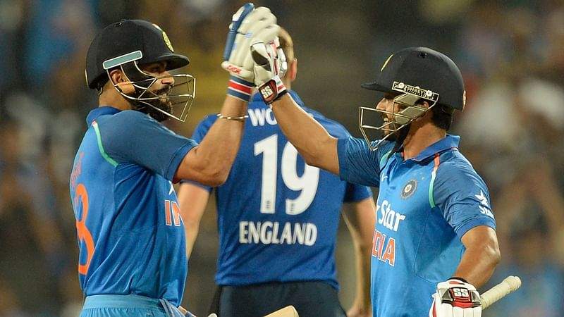 India's Kedar Jadhav (R) celebrates with captain Virat Kohli after scoring a century (100 runs) during the first one-day international cricket match between India and England at The MCA International Cricket Stadium in Pune on January 15, 2017.