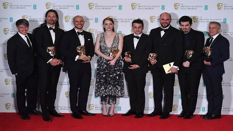 US film producers Fred Berger (3L), Jordan Horowitz (3R) and Marc Platt (R) pose with the award for Best Film for 'La La Land', alongiside US actress Emma Stone (C), US director Damien Chazelle (2R), Swedish cinematographer Linus Sandgre (2L), US composer Justin Hurwitz (4R), at the BAFTA British Academy Film Awards at the Royal Albert Hall in London on February 12, 2017. / AFP PHOTO / Ben STANSALL