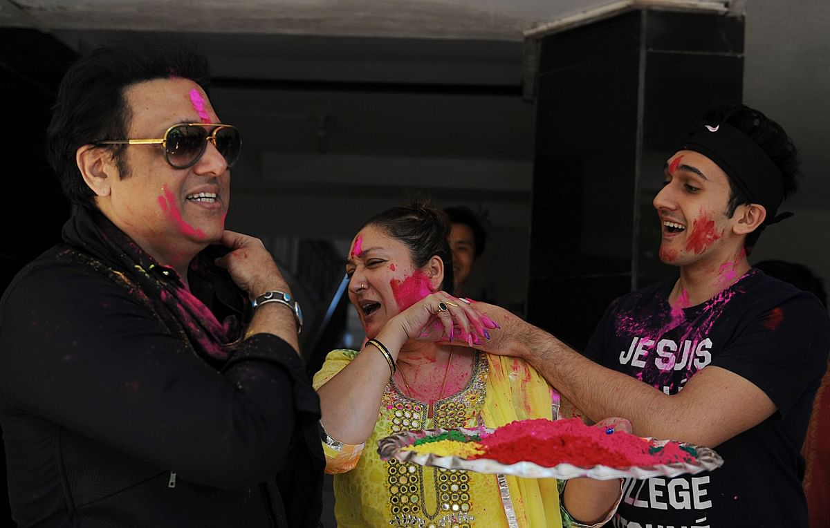 Indian Bollywood actor Govinda (L) with his wife (C) Sunita and son Yashvardhan Ahuja (R) take part in celebrations to mark the Hindu festival of Holi in Mumbai