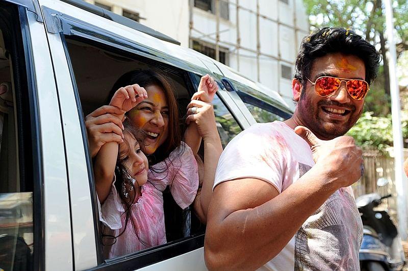 Indian Bollywood actor Sharad Kelkar (R) with wife actress Keerti Gaekwad Kelkar takes part in celebrations to mark the Hindu festival of Holi in Mumbai