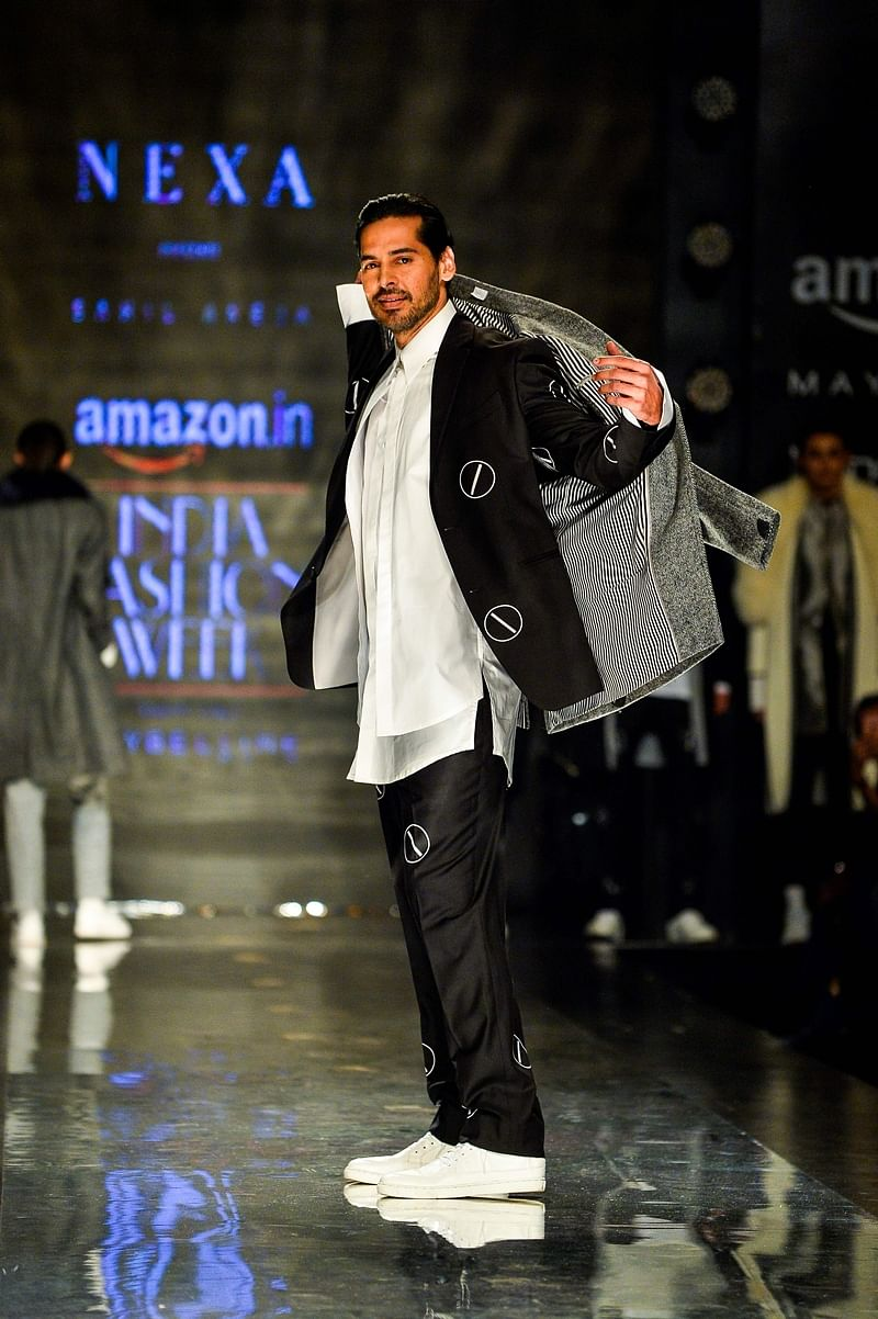 Indian actor Dino Morea presents a creation by Indian designer Sahil Aneja during the Amazon India Fashion Week Autumn Winter 2017 in New Delhi. / AFP PHOTO / CHANDAN KHANNA