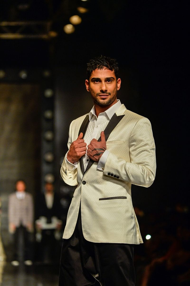 Indian actor Prateik Babbar presents a creation by Indian designers Kommal and Ratul Sood during the Amazon India Fashion Week Autumn Winter 2017 in New Delhi. / AFP PHOTO / CHANDAN KHANNA