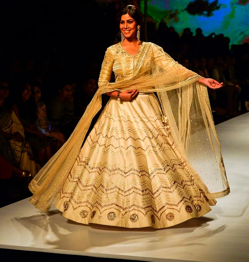 Indian television and film actress Sakshi Tanwar presents a creation by Indian designer Anju Modi during the Amazon India Fashion Week Autumn Winter 2017 on March 17, 2017 in New Delhi. / AFP PHOTO / CHANDAN KHANNA